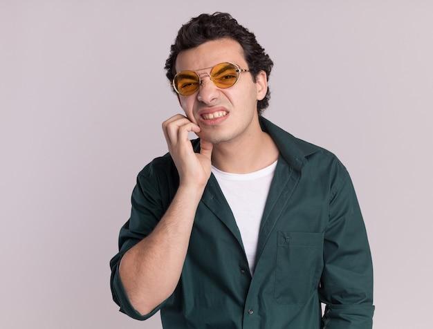 Junger mann im grünen hemd, das eine brille trägt, die verwirrt schaut und sein gesicht kratzt, das über weißer wand steht