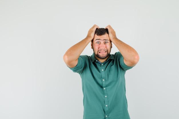 Junger mann im grünen hemd, das hand auf dem kopf hält und beunruhigt aussieht, vorderansicht.