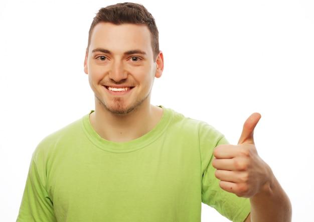 Junger mann im grünen hemd, das sich daumen zeigt.