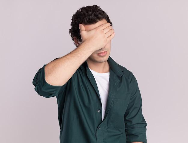Junger mann im grünen hemd müde und gelangweilt schließende augen mit der hand, die über weißer wand steht