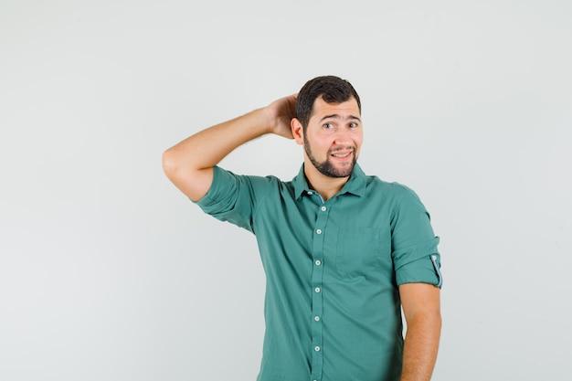 Junger mann im grünen hemd posiert, während er die hand auf dem kopf hält und gutaussehend aussieht, vorderansicht.