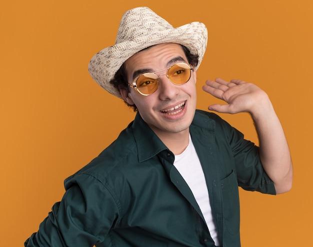 Junger mann im grünen hemd und im sommerhut, der die brille trägt, die glücklich und positiv beiseite schaut, mit erhöhtem arm, der über orange wand steht