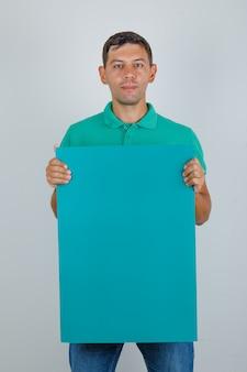 Junger mann im grünen t-shirt, das blaues plakat, vorderansicht hält.
