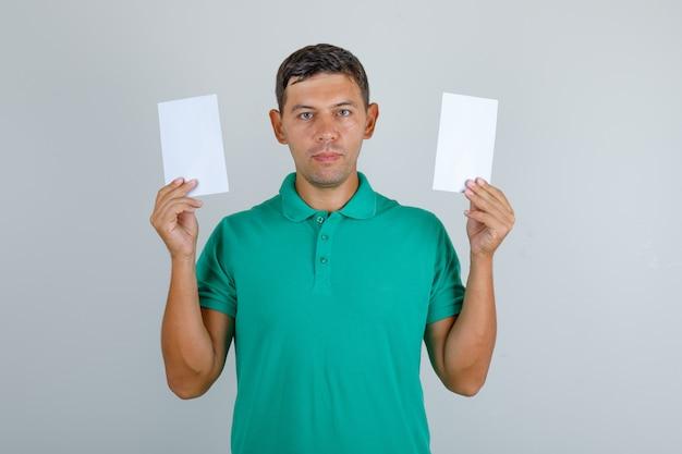 Junger mann im grünen t-shirt, das leere papierblätter, vorderansicht hält.