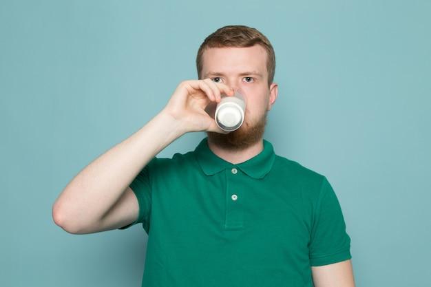 Junger mann im grünen t-shirt trinkglas mit milch