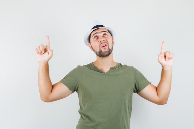 Junger mann im grünen t-shirt und im hut, der oben zeigt und dankbar aussieht