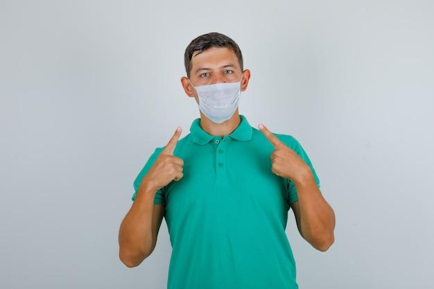 Junger mann im grünen t-shirt zeigt seine medizinische maske und schaut vorsichtig, vorderansicht.