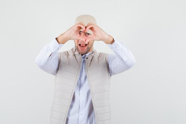 Junger mann im hemd, ärmellose jacke, kappe, die friedensgeste zeigt und liebenswert aussieht.