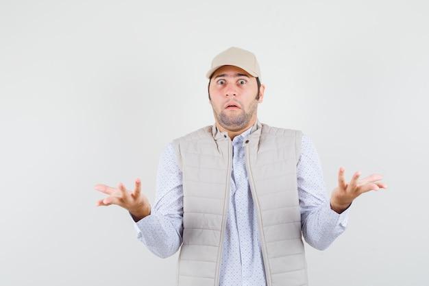 Junger mann im hemd, ärmellose jacke, mütze spreizt offene handflächen beiseite mit fragender art und sieht besorgt aus, vorderansicht.