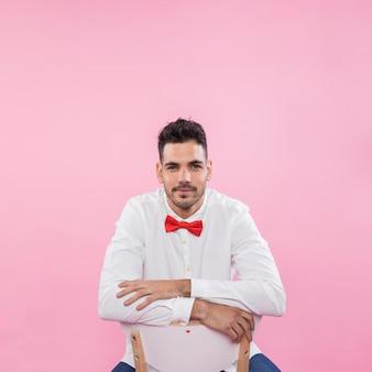 Junger mann im hemd, das auf stuhl sitzt