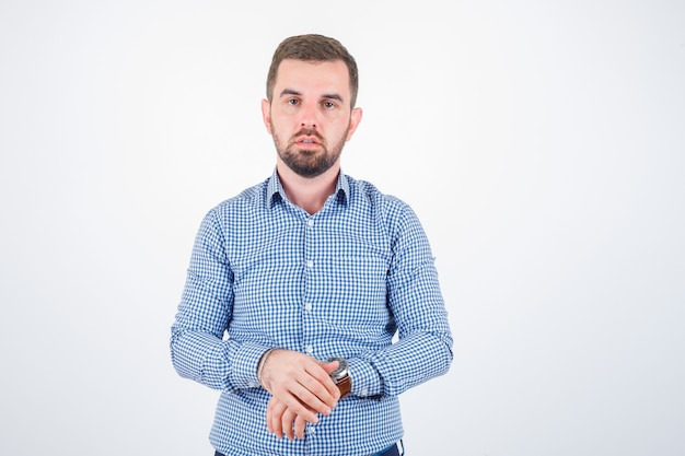 Junger mann im hemd, das beim betrachten der kamera aufwirft und selbstbewusst, vorderansicht schaut.