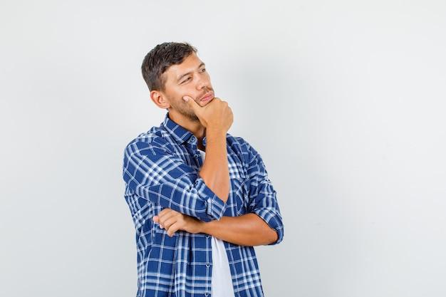 Junger mann im hemd, das beiseite schaut, während kinn hält und nachdenklich, vorderansicht schaut.