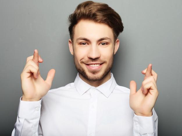 Junger mann im hemd, das finger bei der stellung gekreuzt hält