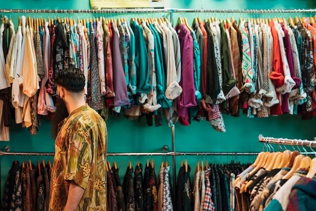 Junger mann im hemd, das kleidung im mall oder im bekleidungsgeschäft wählt