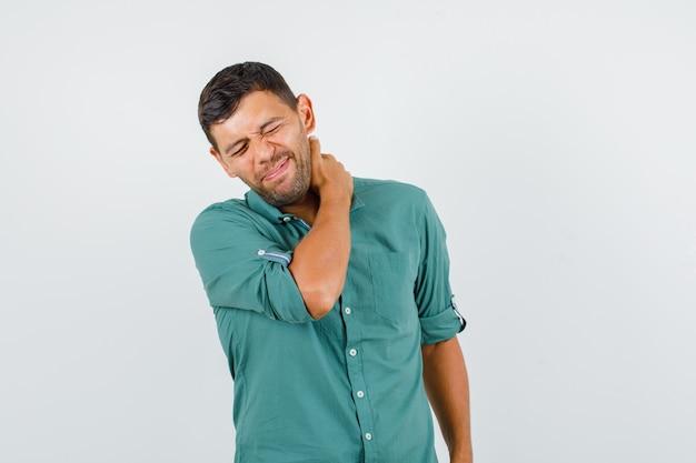 Junger mann im hemd, das unter schmerzen im nacken leidet