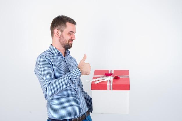 Junger mann im hemd, der geschenkbox hält, während daumen oben zeigt und erfreut, vorderansicht schaut.