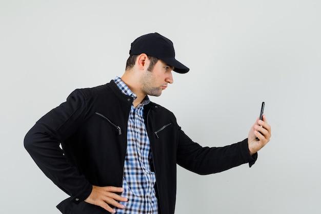 Junger mann im hemd, in der jacke, in der mütze, die auf video-chat sprechen und ernst schauen