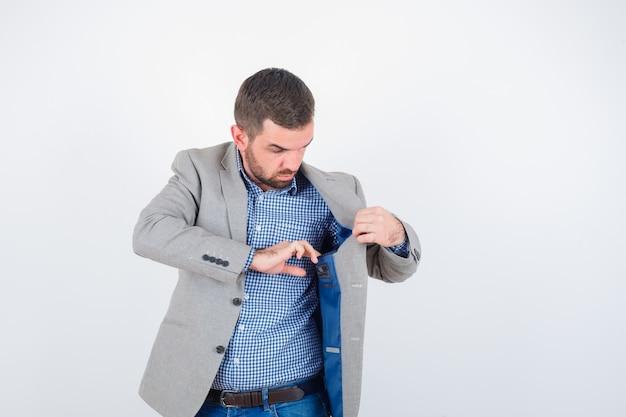Junger mann im hemd, in der jeans, in der anzugjacke, die tasche der jacke betrachtet und ernst schaut, vorderansicht.