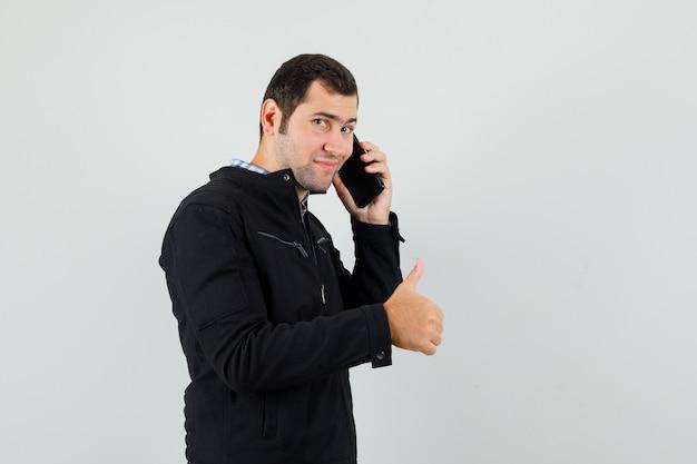Junger mann im hemd, jacke, die auf handy spricht, daumen hoch zeigt und lustig schaut
