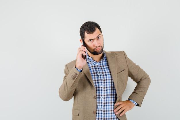 Junger mann im hemd, jacke, die auf handy spricht und ernst schaut, vorderansicht.