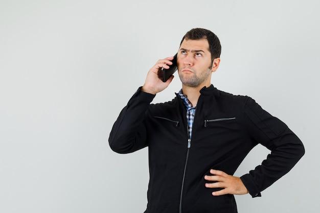 Junger mann im hemd, jacke, die auf handy spricht und unentschlossen schaut