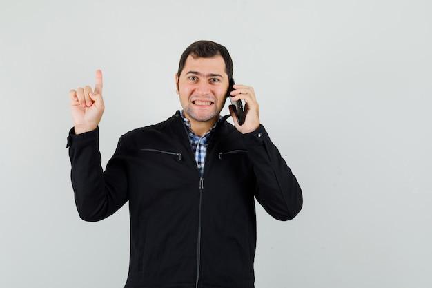 Junger mann im hemd, jacke, die auf handy spricht, zeigt und fröhlich schaut