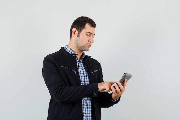 Junger mann im hemd, jacke, die berechnungen auf taschenrechner macht und beschäftigt schaut