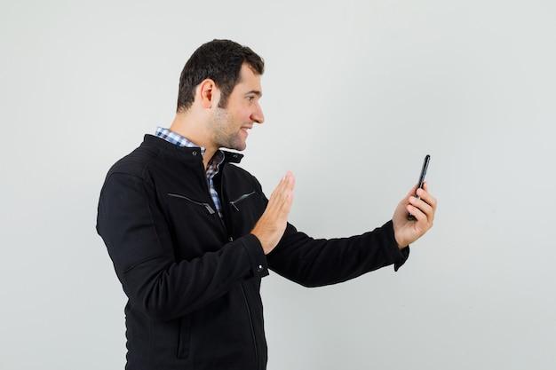 Junger mann im hemd, jacke, die hand auf video-chat winkt und fröhlich schaut