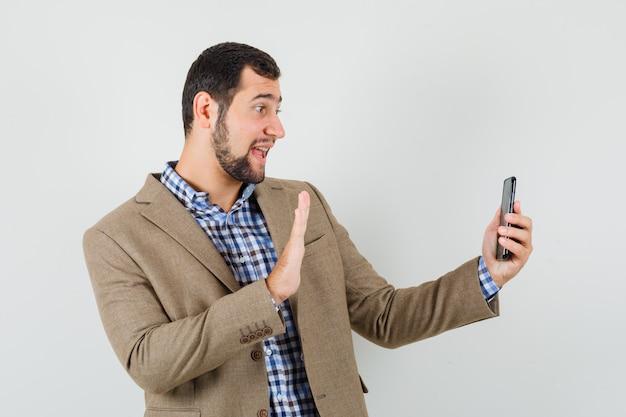 Junger mann im hemd, jacke, die hand auf video-chat winkt und fröhlich, vorderansicht schaut.