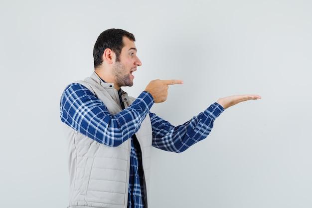 Junger mann im hemd, jacke zeigt auf die linke seite, zeigt etwas und sieht konzentriert, vorderansicht.