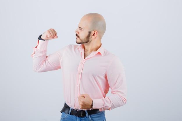 Junger mann im hemd, jeans, die armmuskeln zeigt und stolz aussieht, vorderansicht.