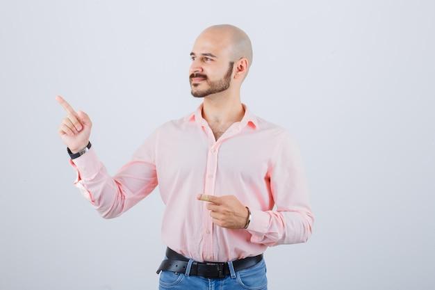 Junger mann im hemd, jeans, die beiseite zeigen und glücklich aussehen, vorderansicht.