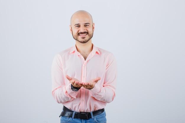 Junger mann im hemd, jeans, die hohle hände ausdehnt und friedlich aussieht, vorderansicht.