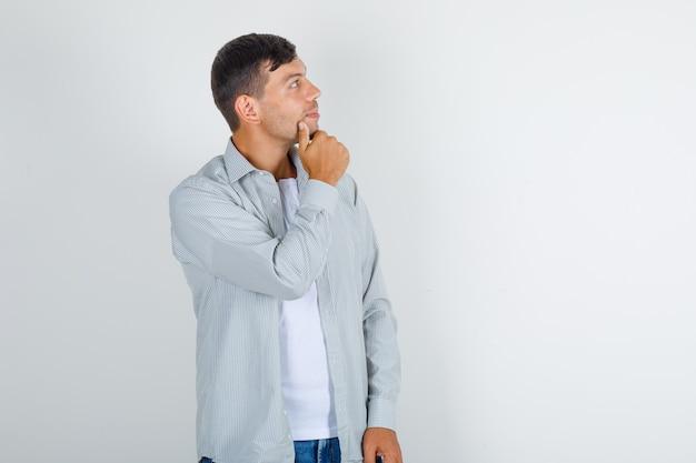 Junger mann im hemd, jeans, die mit hand am kinn nach oben schauen