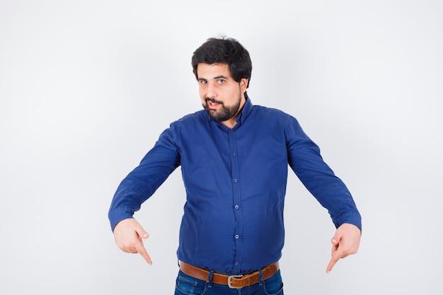 Junger mann im hemd, jeans, die nach unten zeigen und optimistisch aussehen, vorderansicht.