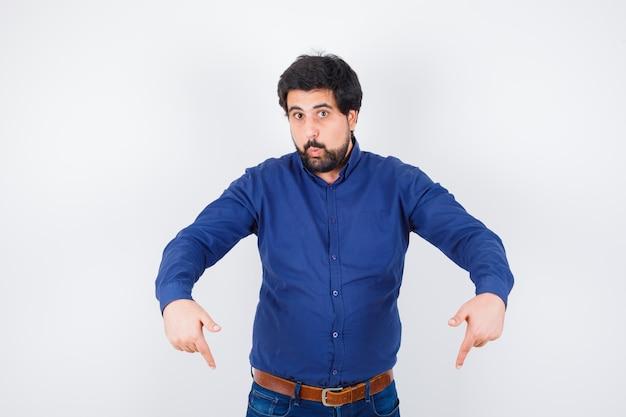 Junger mann im hemd, jeans, die nach unten zeigen und positiv aussehen, vorderansicht.