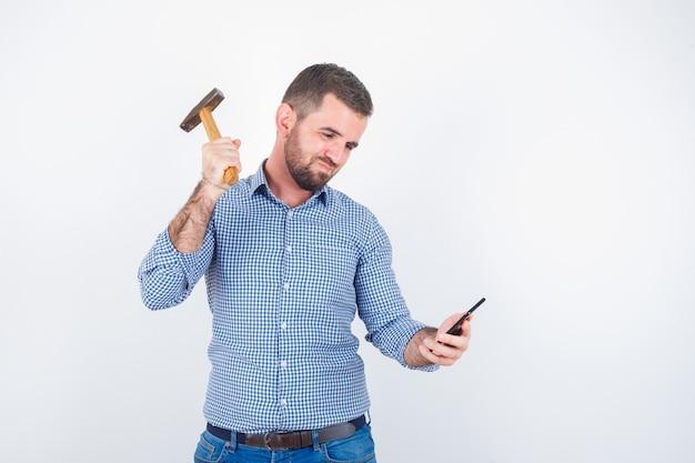 Junger mann im hemd, jeans, die vorgibt, handy mit einem hammer zu schlagen und ernst zu schauen, vorderansicht.