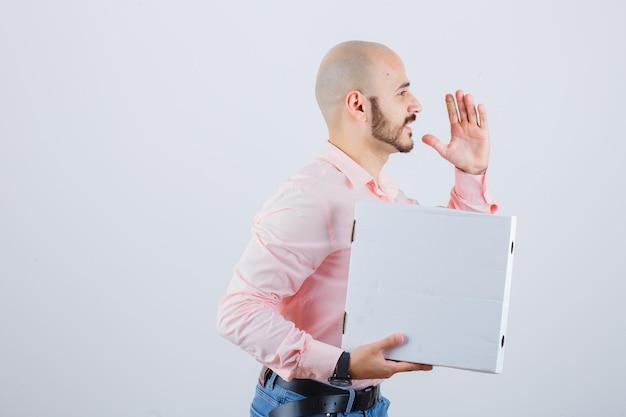 Junger mann im hemd, jeans läuft mit pizzakarton und sieht selbstbewusst aus, vorderansicht.