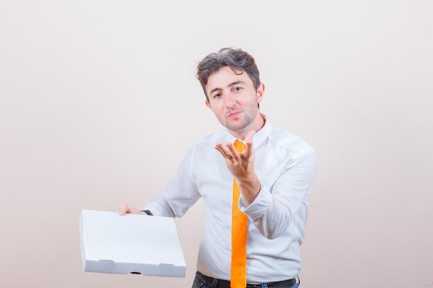 Junger mann im hemd, jeans mit pizzakarton, hand heben in erfreuter geste