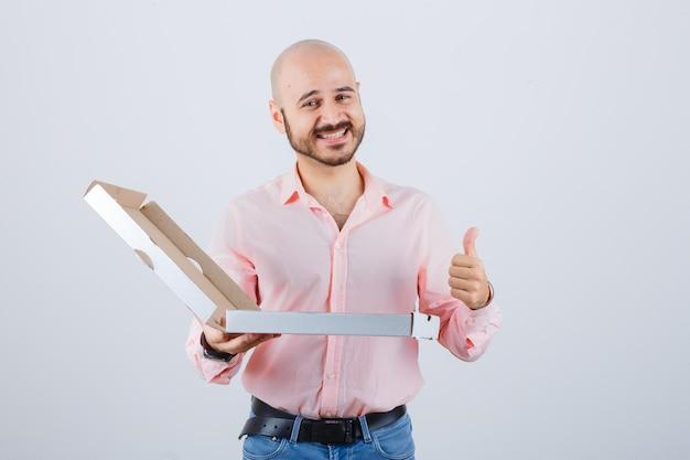 Junger mann im hemd, jeans zeigt daumen nach oben und sieht selbstbewusst aus, vorderansicht.