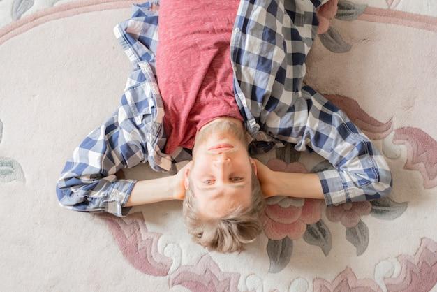 Junger mann im hemd lag auf dem teppich und entspannte sich nach einem anstrengenden tag