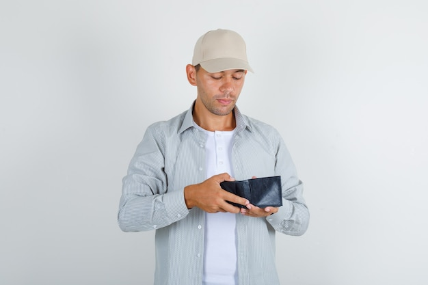Junger mann im hemd mit kappe, die in geöffnete brieftasche schaut und vorsichtig schaut