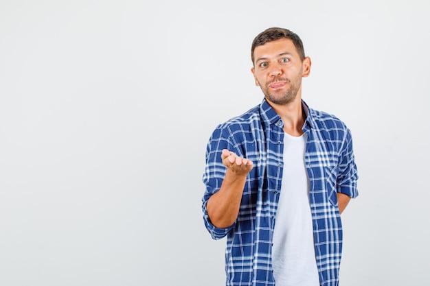Junger mann im hemd spreizt offene handfläche in richtung und schaut lustig, vorderansicht.