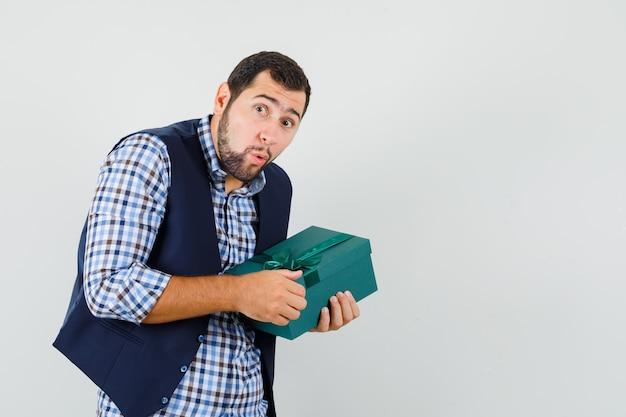 Junger mann im hemd, weste, die versucht, geschenkbox zu öffnen und neugierig, vorderansicht schauend.