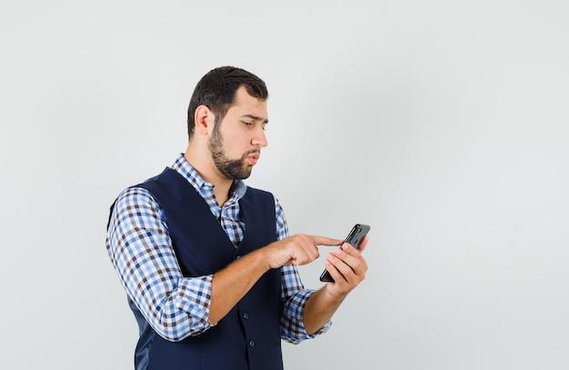 Junger mann im hemd, weste mit handy und blick beschäftigt, vorderansicht.