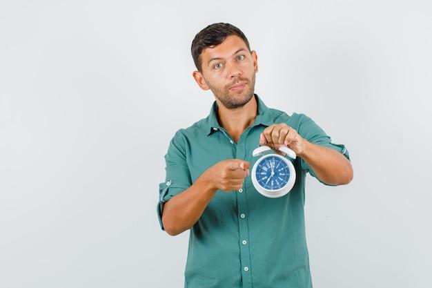 Junger mann im hemd zeigt auf kamera mit wecker