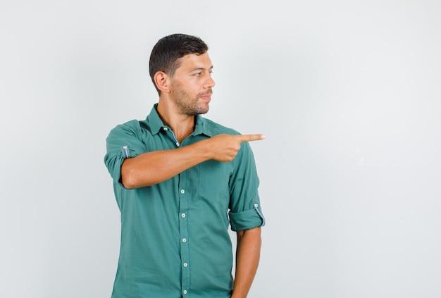 Junger mann im hemd zeigt zur seite