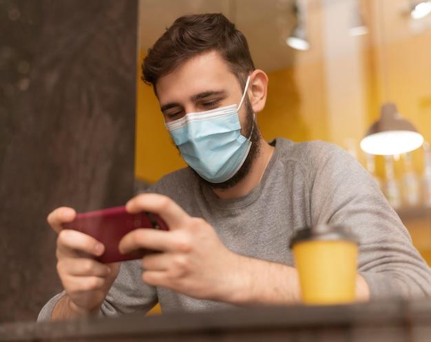 Junger mann im kaffeehaus, der eine medizinische maske trägt