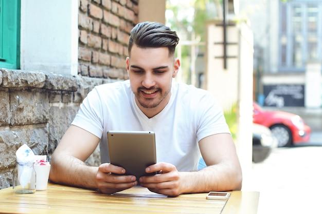 Junger mann im kaffeestubekaffee unter verwendung einer tablette.