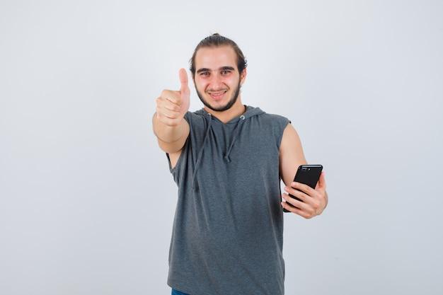 Junger mann im kapuzen-t-shirt, das daumen oben zeigt und erfreut, vorderansicht schaut.